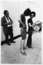 Adrian Piper Getting Back #1, July 1975. B/W photo documentationof a street performance in Cambridge